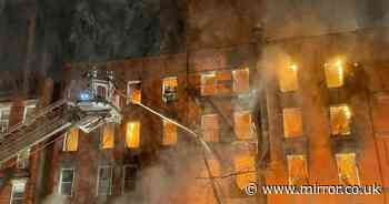 Massive fire engulfs entire five-storey building and spreads to historic church