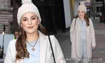 Kelly Brook wraps up warm in a cream coat and loungewear as she arrives for work at Heart Radio