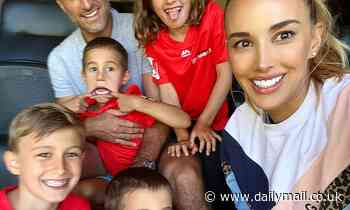 Bec Judd looks delighted on family day out at the cricket with husband Chris and their children