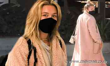 Florence Pugh cozies up in peachy pink as she touches down at the airport