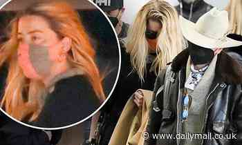 Amber Heard keeps her head down as she arrives at LAX with her girlfriend Bianca Butti