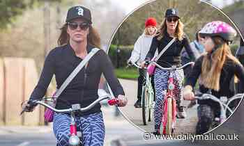 Amanda Holden cuts a sporty figure as she enjoys a family bike ride with daughters Alexa and Hollie