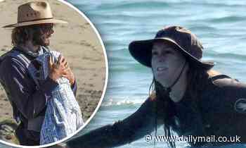 Surf's up! Leighton Meester paddles out into the Malibu waves while Adam Brody cradles their son