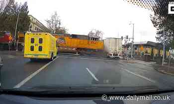 Moment train plows into a big rig on a crossing after trucker drives past safety barriers