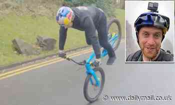 Stunt cyclist balances on his front wheel and rides down a hill BACKWARDS