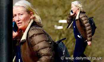 Emma Thompson wears a padded brown coat and blue dungarees as she enjoys a stroll