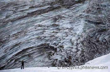 A tourist poses for a picture on the Bogdanovich glacier - in-cyprus