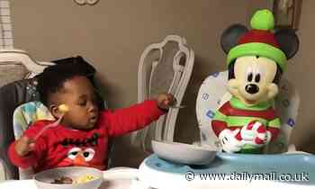 Sharing is caring! Adorable toddle offers his scrambled eggs to his Mickey Mouse doll