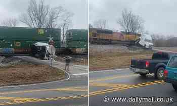 Large semi truck stuck on railroad tracks is split into two by oncoming train in Georgia