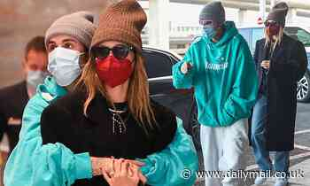 Justin and Hailey Bieber cosy up while wearing face masks as they arrive at Paris airport
