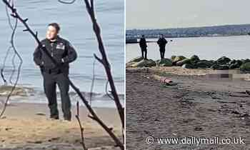 Two Canadian police officers filmed posing for photos in front of dead man