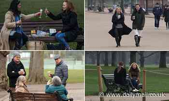 Friends celebrate day one of the Great Unlocking with a bottle of fizz on a park bench