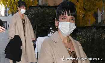Lily Allen steps out in a long tan coat and white trainers as she heads to dinner in London