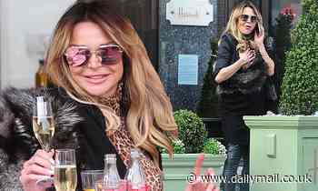 Lizzie Cundy exudes glamour in a fur-look stole and faux leather jeans as she sips champagne