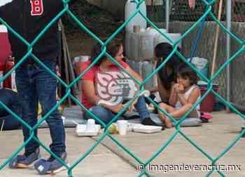 Mujeres y niños comen en el suelo en retén migratorio del sur - Imagen de Veracruz