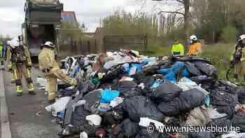 Chauffeur vuilniswagen lost lading afval langs de weg nadat die vuur vatte