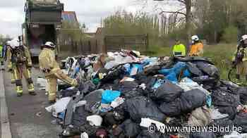 Chauffeur vuilniswagen lost lading brandend afval langs de weg