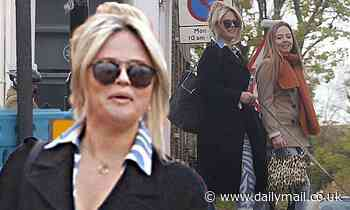 Emily Atack cuts stylish figure in black belted coat and patterned jumpsuit on walk with friend