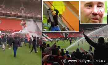 Angry Manchester United fans STORM onto the pitch at Old Trafford