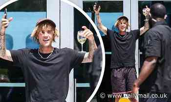 Justin Bieber greets fans in Miami while holding a glass of wineand a skateboard