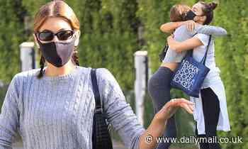 Kaia Gerber shows off her toned midriff and hugs a female friend after Pilates class in LA