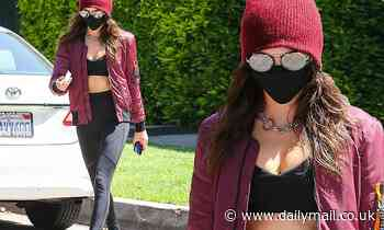 Cara Delevingne showcases her toned tummy in a black sports bra and leggings in Los Angeles