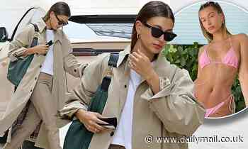 Hailey Bieber covers her supermodel figure in a Burberry rain coat even though there's not a cloud
