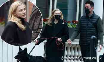 Chloe Grace Moretz wraps up in a black coat as she takes her dog for a walk around London