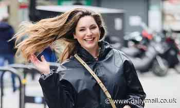 Kelly Brook playfully whips her freshly styled locks around after visiting hairdresser