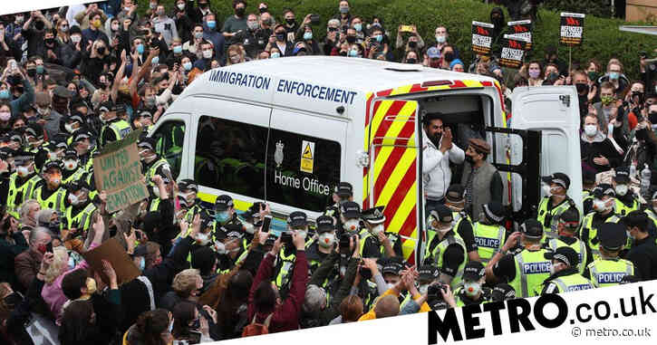 Cheers as police release men from immigration van after protesters block road