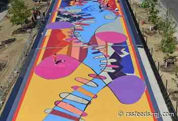 PHOTOS: See volunteers bring Brad Carney's mural 'Locomotion' to life on Reno's ReTRAC Plaza