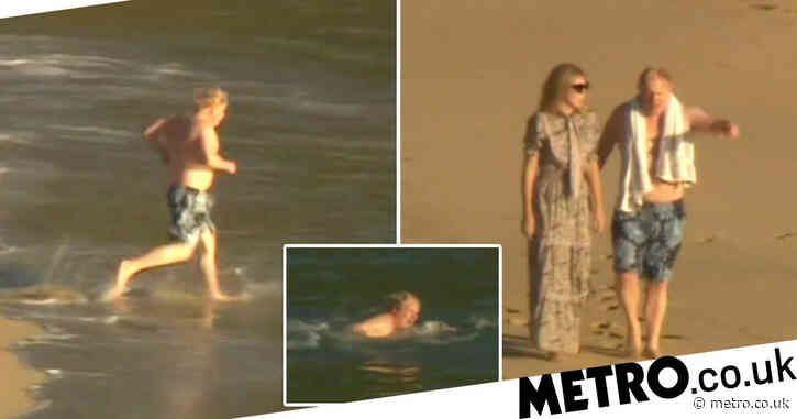 Boris and Carrie stroll along the beach after PM takes another dip in the sea