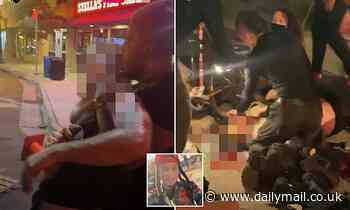 Driver plows into protesters and kills woman before he is pulled from car and beaten