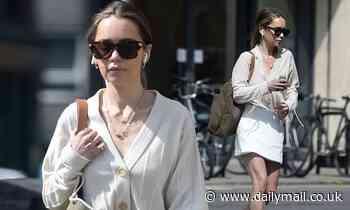 Emilia Clarke puts on a leggy display in white mini skirt
