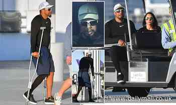 Tiger Woods is seen hobbling on crutches four months after horror car crash