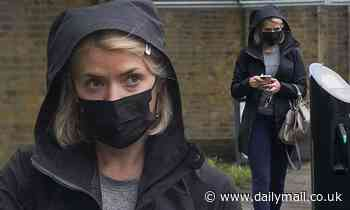 Holly Willoughby braves the bad weather as she heads out in gym leggings and a black hooded jacket