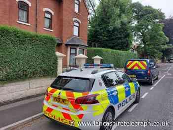 Police vehicles outside set of flats in Blackburn