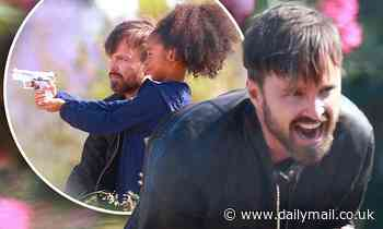 Breaking Bad vet Aaron Paul teaches a young girl how to fire a gun while filming project