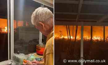 Super calm man casually peels carrots as a huge fire rages just behind his house