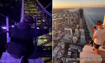 Daredevils risk death as they are spotted taking videos from the top of Australia's tallest building