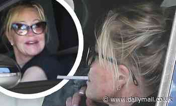 Melanie Griffith is seen smoking a cigarette on her drive home after hitting the gym inLos Angeles