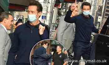Hugh Jackman pulls a peace sign as he steps out in New York after returning to America - Daily Mail