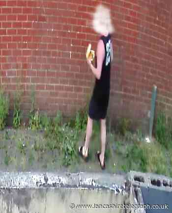 Man urinates on wall whilst munching on burger
