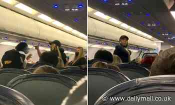 The wild moment a woman in her seat on a Spirit Airlines flight punches and grabs another woman