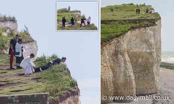Dicing with death... for a selfie: Tourists pose for photographs on edge of crumbling cliff