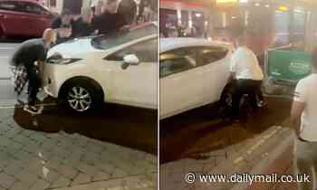 Burly lads on a night out LIFT car out of tram's way after driver parks on the line