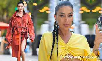 Nicole Williams flashes her tummy in yellow dress before modeling a baggy orange outfit