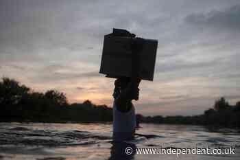 Harrowing photos at Texas border show desperate Haitian migrants crossing river with belongings