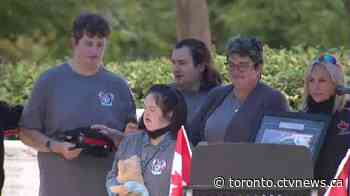 Three children of fallen Toronto police officer given hats with father's badge number at memorial