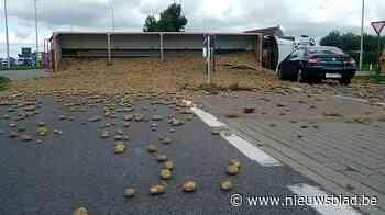 Vrachtwagen kantelt op rotonde, aardappelen rollen over auto